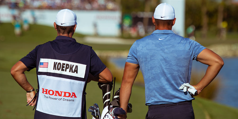 Brooks Kopeka standing next to caddie